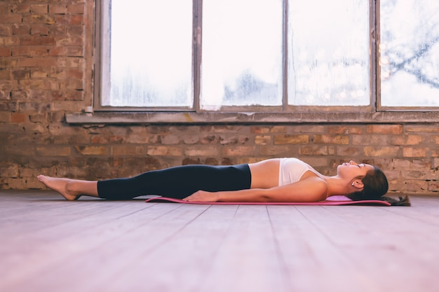 Młoda kobieta leżąca w pozycji spoczynkowej shavasana na podłodze