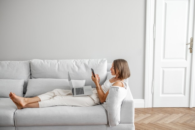 Młoda kobieta leżąca zrelaksowana z telefonem i laptopem na wygodnej kanapie