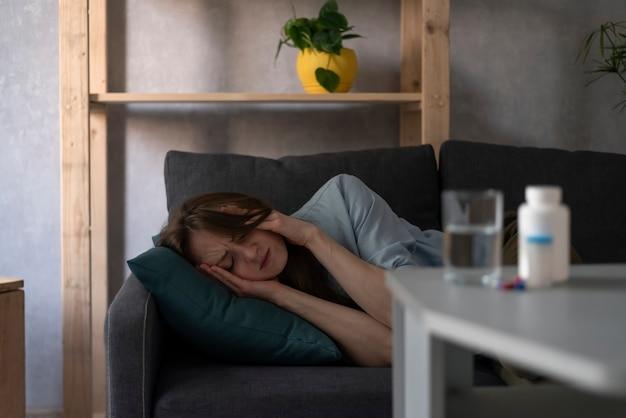 Młoda kobieta leży i trzyma głowę rękami, tabletki na stole. ból głowy, migrena, kac.