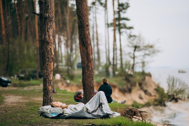 Młoda kobieta leży na brzegu małego jeziora pod lasem