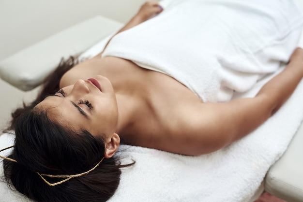 Młoda kobieta leży na kanapie obok kosmetyczki lub masażysty. rozpięte włosy i szlafrok. pielęgnacja skóry twarzy. kobieta w salonie piękności spa.