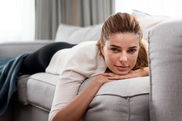 Młoda kobieta leży na kanapie w domu