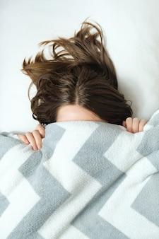 Młoda kobieta leży w łóżku pod kocem i ciężko się budzi rano. pojęcie problemów z przebudzeniem ze snu.