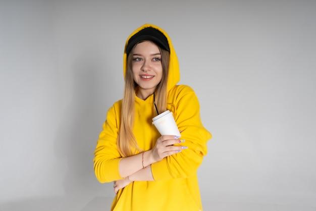 Młoda kobieta lgbtq uśmiechnięta szeroko na sobie żółtą bluzę z kapturem trzymająca filiżankę kawy