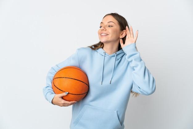 Młoda kobieta litewska gra w koszykówkę na białym tle słuchając czegoś, kładąc rękę na uchu