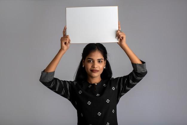 Młoda kobieta lub bizneswoman trzyma tablicę w dłoniach na szarym tle.