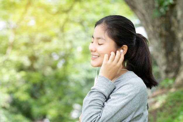 Młoda kobieta lubi muzykę i trzyma ręce na słuchawkach na zewnątrz.