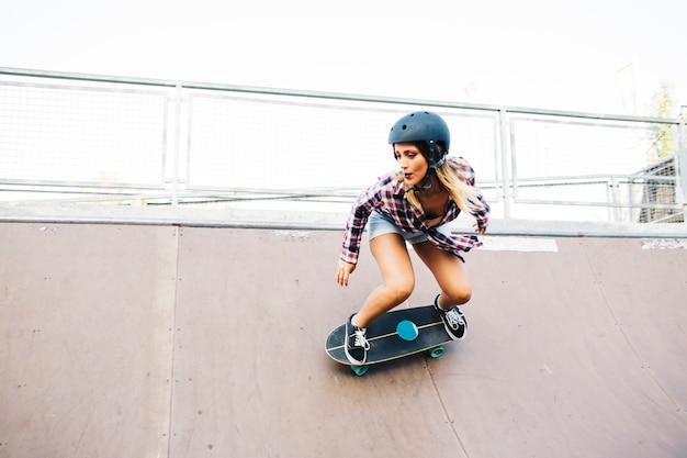 Młoda kobieta łyżwiarstwo w połowie rury z kasku