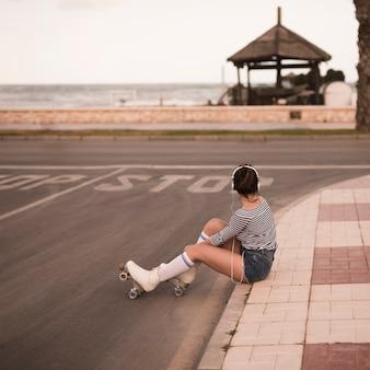 Młoda kobieta łyżwiarz siedzi na chodniku słuchania muzyki na słuchawkach patrząc od hotelu