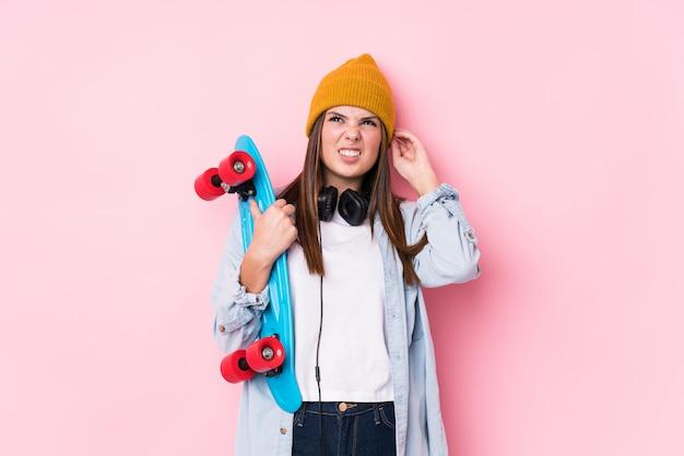 Młoda kobieta łyżwiarz trzyma łyżwy obejmujące uszy rękami.