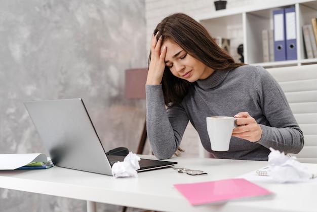 Młoda kobieta ma ból głowy podczas pracy w domu