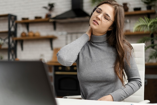 Młoda kobieta ma ból szyi podczas pracy w domu