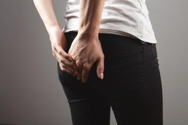 Młoda kobieta ma hemoroidy na szarym tle