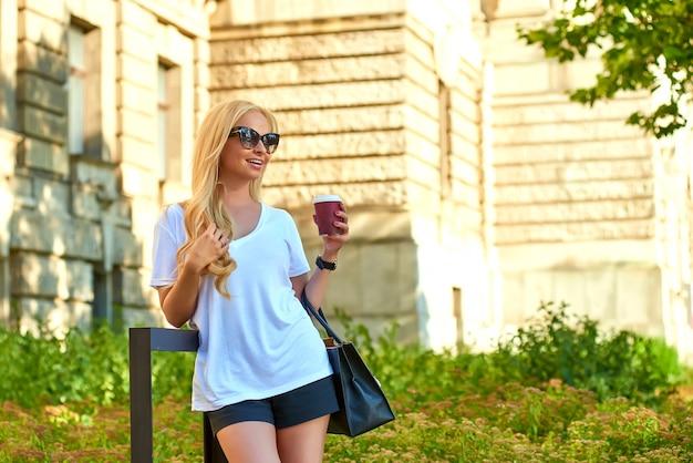 Młoda kobieta ma kawę przed starym budynkiem