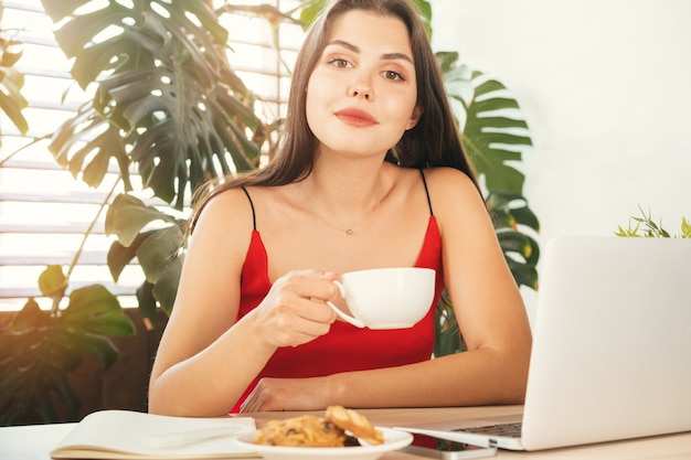 Młoda kobieta ma kawową przerwę podczas gdy siedzący w jej biurze