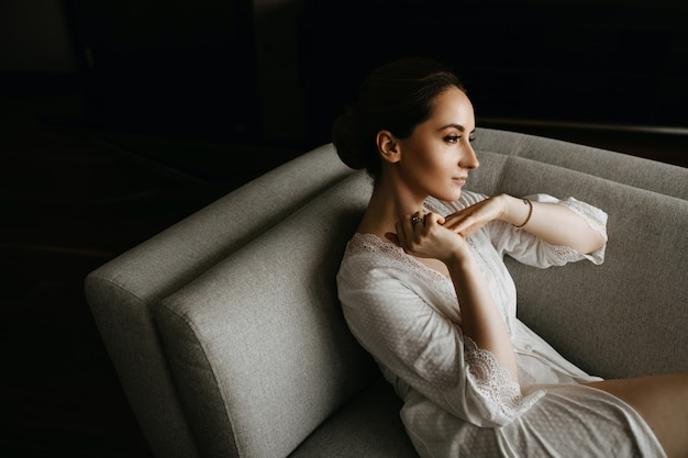 Młoda kobieta ma na sobie białą jedwabną szatę, siedząc na kanapie. spokojny nastrój.