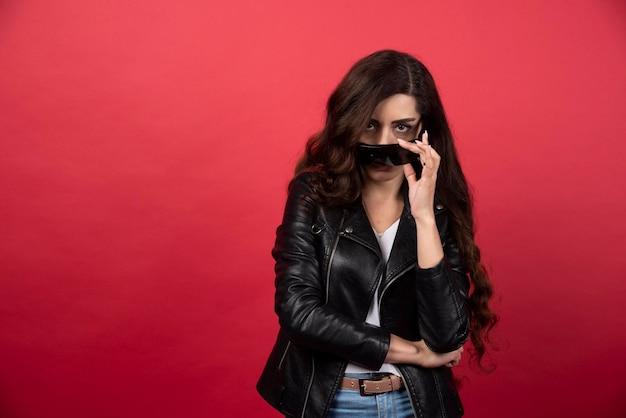 Młoda kobieta ma na sobie czarne okulary na czerwonym tle. zdjęcie wysokiej jakości