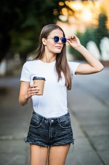 Młoda kobieta ma na sobie krótką białą koszulę i okulary przeciwsłoneczne chodzące z kawą na ulicę