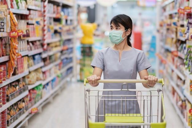 Młoda kobieta ma na sobie ochronną maskę na twarz i zakupy