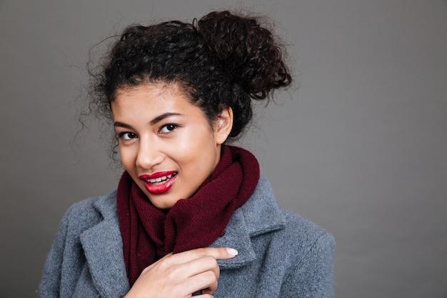 Młoda kobieta ma na sobie płaszcz i szalik