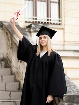 Młoda kobieta ma na sobie suknię ukończenia szkoły