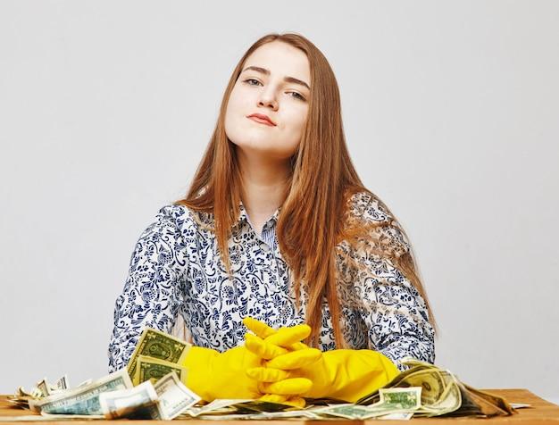 Młoda kobieta ma na sobie żółte gumowe rękawiczki i trzyma głowę do góry