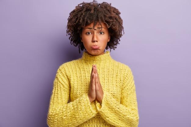 Młoda kobieta ma na sobie żółty sweter z fryzurą afro