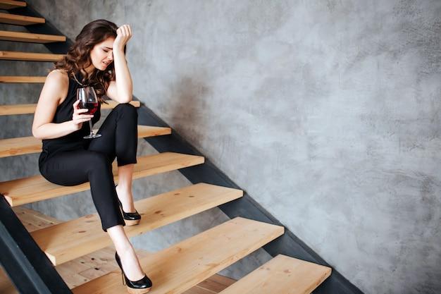 Młoda kobieta ma problemy z alkoholem. siedząc samotnie na schodach. po kacu. w ręku trzyma kieliszek czerwonego wina. cierpi na ból głowy. kobieta po spotkaniach.