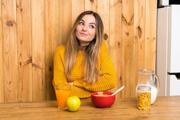 Młoda kobieta ma śniadanie w kuchni robi wątpliwości gestowi podczas gdy podnoszący ramiona