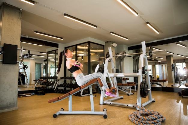 Młoda kobieta ma trening na ławce w siłowni