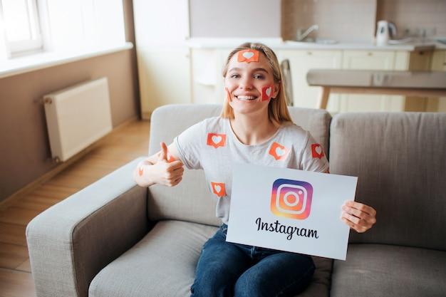Młoda kobieta ma uzależnienie od mediów społecznościowych. uzależnienie od smartfonów. młoda kobieta siedzi na kanapie w salonie i uśmiech. jak symbol. szczęśliwa pozytywna kobieta.