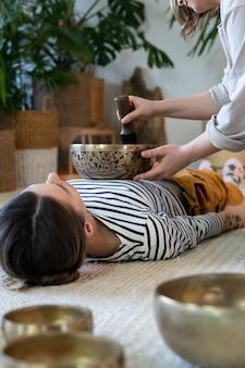 Młoda kobieta ma w domu terapię miską do masażu tybetańskiego z tradycyjnymi talerzami z brązu tybetańskiego