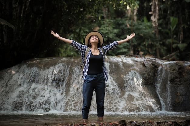 Młoda kobieta ma zabawę pod siklawami w lesie