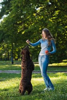 Młoda kobieta ma zabawę z jej psem w ogródzie
