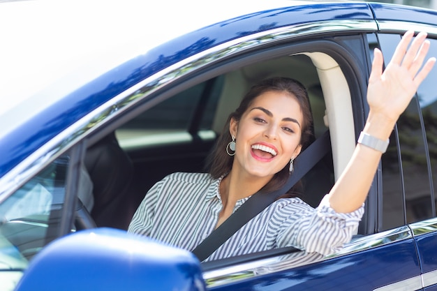 Młoda kobieta macha. piękna młoda kobieta prowadząca samochód machający podczas spotkania z przyjacielem na ulicy
