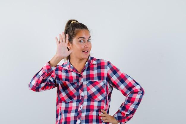 Młoda kobieta macha ręką, by się pożegnać w dorywczo koszuli i wygląda na szczęśliwego. przedni widok.