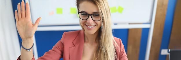 Młoda kobieta macha ręką na ekranie komputera w biurze