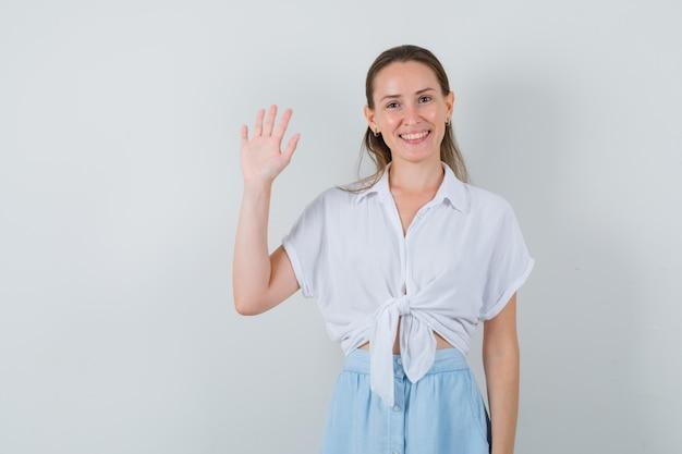 Młoda kobieta macha ręką na powitanie w bluzkę i spódnicę i szuka jowialnego