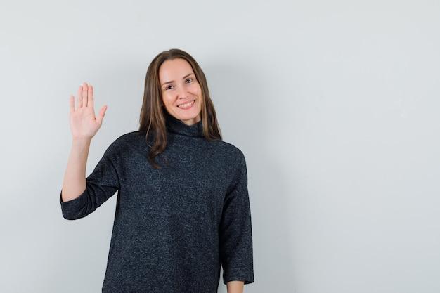 Młoda kobieta macha ręką na powitanie w koszuli i wygląda wesoło