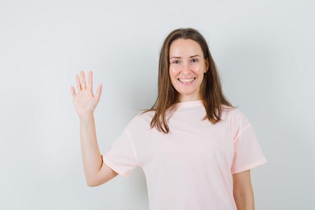 Młoda kobieta macha ręką na powitanie w różowej koszulce i szuka wesołej. przedni widok.
