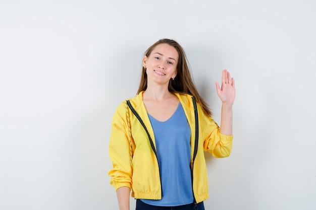 Młoda kobieta macha ręką na pożegnanie w t-shirt i wygląda wesoło. przedni widok.
