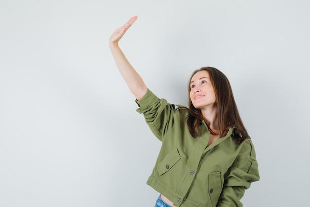 Młoda kobieta macha ręką, patrząc w kurtkę, widok z przodu.
