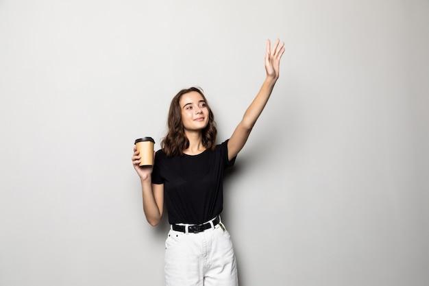 Młoda kobieta macha ręką podczas chodzenia i trzymając kubek z kawą na białym tle na szarym tle