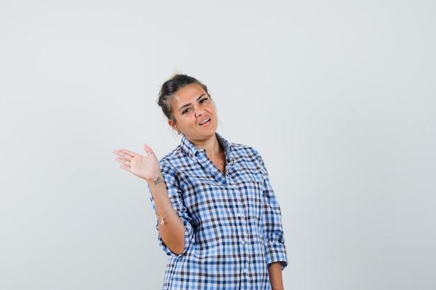 Młoda kobieta macha ręką żegnając się w kraciastej koszuli.