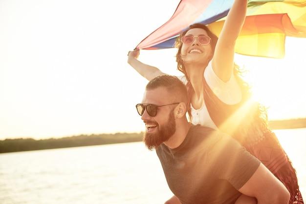 Młoda kobieta machająca tęczową flagą na męskich ramionach