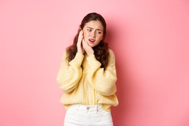 Młoda kobieta mająca ból zęba, dotykająca spuchniętego policzka i krzywiąca się z bólu, potrzebuje wizyty u dentysty, wizyta u stomatologa, stojąca przed różową ścianą