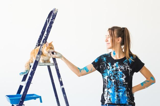 Młoda kobieta malarz głaszcząc kota, projektant i robotnik maluje ścianę.