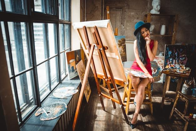 Młoda kobieta malarz w swoim studio robi sztukę