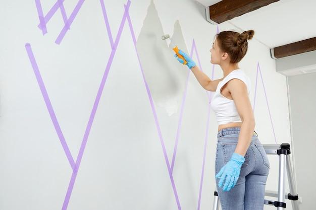Młoda kobieta malująca górski ornament na ścianie za pomocą wałka do malowania, stojąc na drabinie