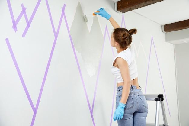 Młoda kobieta malująca góry na ścianie za pomocą wałka do malowania i używająca taśmy maskującej, stojąc na